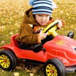 Cute kid driving toy car in the fall